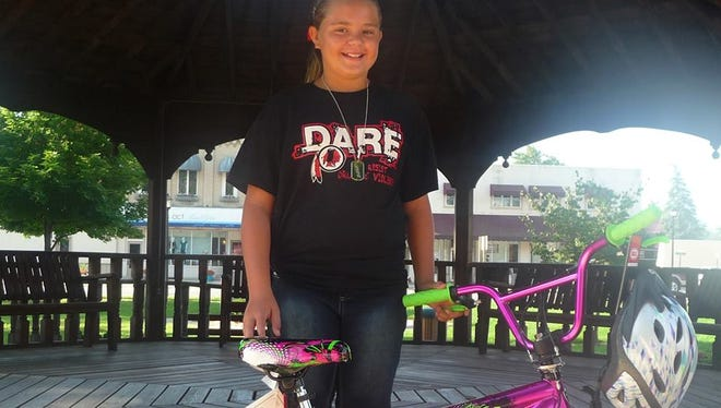 Alyssa Tank, 10, of Sandusky, won a 20-inch freestyle bicycle in the Sanilac County 4-H Fair/D.A.R.E. bicycle drawing Aug. 25. Drug Task Force members and D.A.R.E. instructors answered questions, accepted entries for the bicycle drawing and distributed wrist bands and pencils at the Sanilac County 4-H Fair.