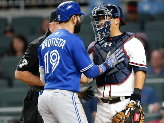 Toronto Blue Jays' Jose Bautista (19) exchanges words with Atlanta Braves catcher Kurt Suzuki (24) after hitting a home run during the eighth inning of a baseball game Wednesday, May 17, 2017, in Atlanta. The incident led to both benches and bullpens emptying onto the field for the second time of the game. Atlanta won 8-4. (AP Photo/John Bazemore)