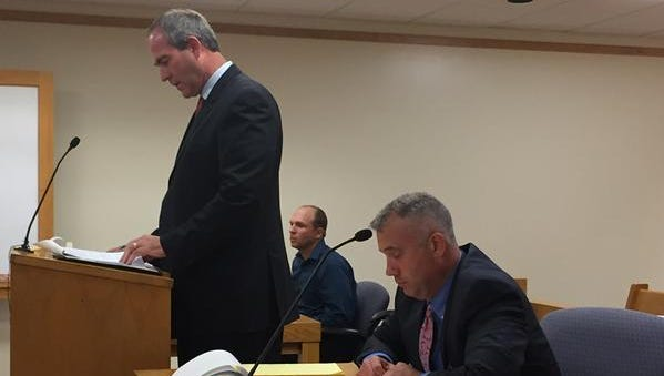 Christopher Scott, center, and his attorneys attend the continuation of his preliminary hearing on a felony animal cruelty charge in Lapeer County District Court on Thursday, July 23, 2015.