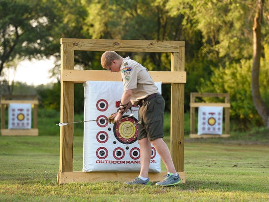 Brian Amundson, 15, pulls arrows out of the target