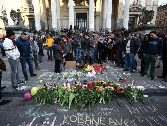 People gather to leave tributes at the Place de la