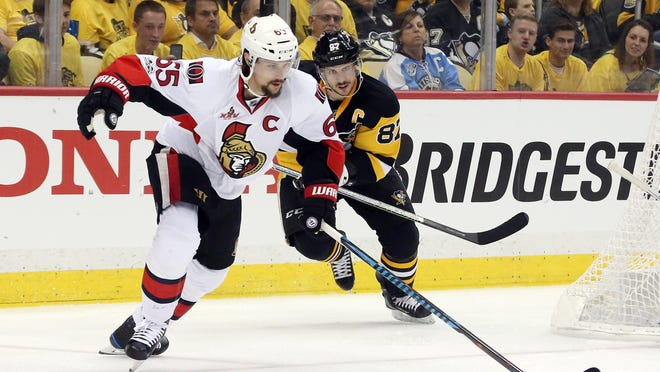 Ottawa Senators defenseman Erik Karlsson (65) skates with the puck as Pittsburgh Penguins center Sidney Crosby (87) chases during the second period in game one of the Eastern Conference Final of the 2017 Stanley Cup Playoffs at PPG PAINTS Arena on May 13, 2017.