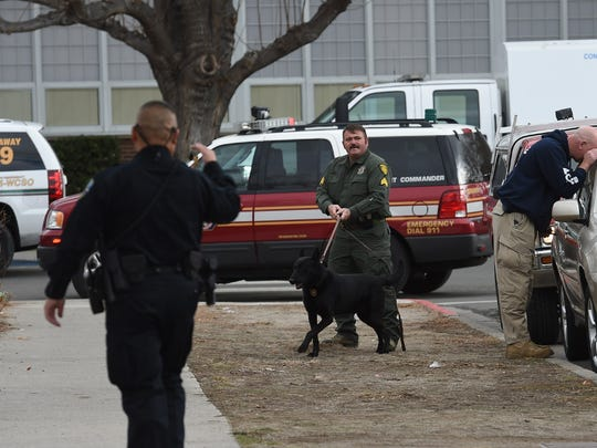 A K-9 is used to search cars parked near Sparks High School. The bomb squad vehicle is parked in the background.