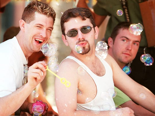 Jeff Andringa (left) lets Travis Edwards have a try at blowing some bubbles in the Nu Towne Saloon Float in Phoenix's 3rd Annual Gay Pride Parade. The float was filled with family, friends and employees.