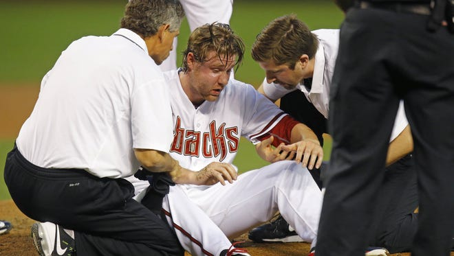 Trainers tend to Arizona Diamondbacks starting pitcher Archie Bradley (25) after he was hit in the face by a line drive during the second inning of their MLB game against  the Colorado Rockies April 28, 2015 in Phoenix.