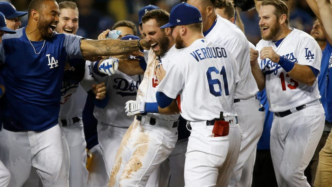 Los Angeles Dodgers' Chris Taylor, center, is mobbed by teammates at home plate after hitting a walk-off solo home run during the 10th inning of a baseball game against the Colorado Rockies in Los Angeles, Tuesday, Sept. 18, 2018. (AP Photo/Alex Gallardo)