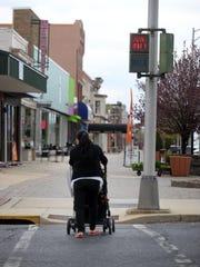 A woman pushes a baby stroller accross 7th Street,