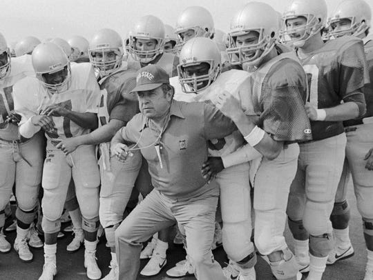 Former CSU football coach Earle Bruce is pictured at Ohio State pushing his players backward behind the line on the practice field where they were beginning laps in 1986.