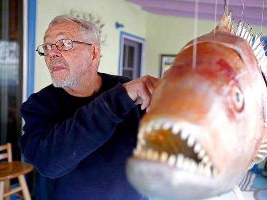 Don Hammontree, 75, of Aztec, describes how he constructed one of his metal fish to move in the wind on Wednesday at his home in Aztec.