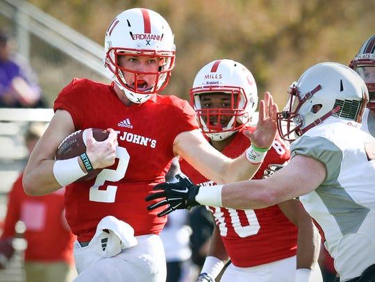 St. John's quarterback Jackson Erdmann tries to push