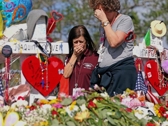 Marjory Stoneman Douglas High School administrative employees Margarita LaSalle, left, and JoEllen Berman, walk along the hill near the school lined with 17 crosses to honor the students and teachers killed on Valentine's Day. Teachers and staff returned to the school, Friday, February 23, 2018, for an orientation and to get ready to receive students next week.  (Charles Trainor Jr/The Miami Herald via AP)