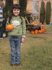Annalyde Morales shows off the pumpkin she picked out when she visited the Grace Methodist Church pumpkin patch Thursday morning with the Bethel Baptist Tots preschool.