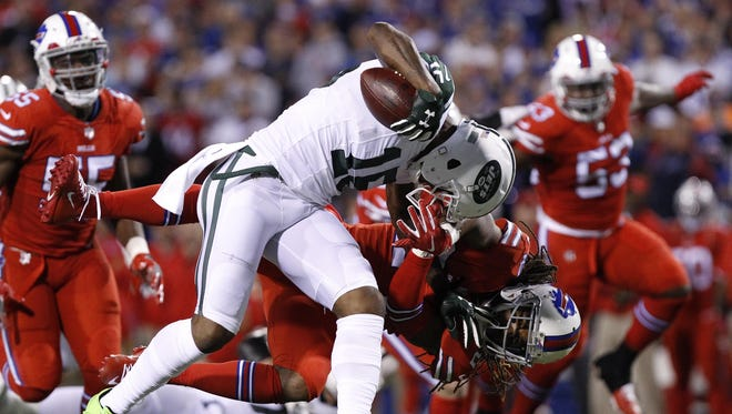 New York Jets wide receiver Brandon Marshall (15) is tackled by Buffalo Bills cornerback Stephon Gilmore (24) during the first half of their game at New Era Field in Orchard Park, New York. Gilmore was called for a face mask penalty in the play.