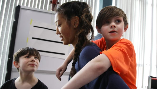 Olivia Soprano, an AutismUp staff member, organizes the next activity for brothers Jordan Banker and Caleb Banker during a fitness class. The staff and kids have formed special bonds over time spent at AutismUp.