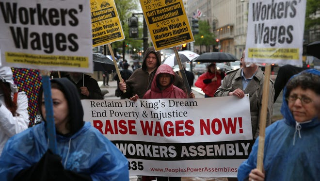 Activists urge a raise in the minimum wage during a protest on April 29 in Washington, D.C.