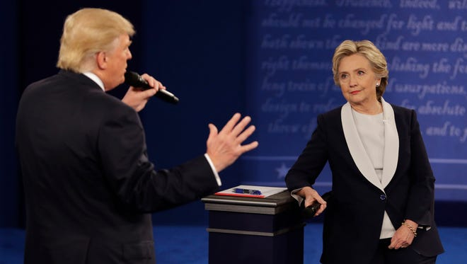 Hillary Clinton listens to Donald Trump during the second presidential debate at Washington University in St. Louis on Oct. 9, 2016.