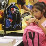 Kimberly Aguilar, 7, grasps her new backpack as she browses the isles for school supplies during Big Backpack Event at the Harborside Event Center in Fort Myers on Sunday.