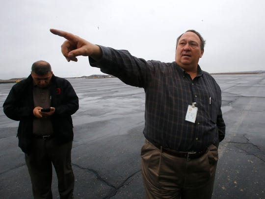 Airport manager Mike Lewis, right, on Wednesday, talks about the closure of a maintenance hangar during an interview at the Four Corners Regional Airport in Farmington. At left is City of Farmington transit manager Andrew Montoya.