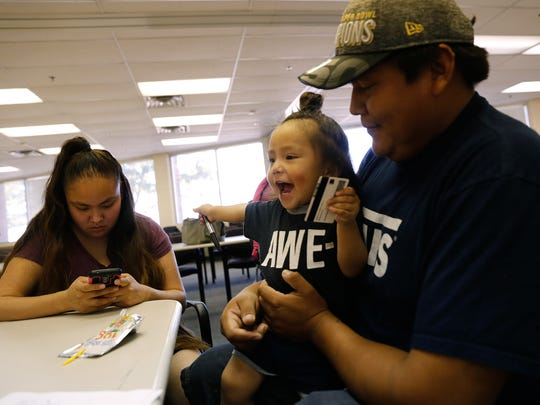 Shenika Sam, left, and Myron Ben fill out paperwork for their son, Mikaiya Ben, for his birth certificate Thursday at the Northern Navajo Agency Nataani Nez Complex in Shiprock.
