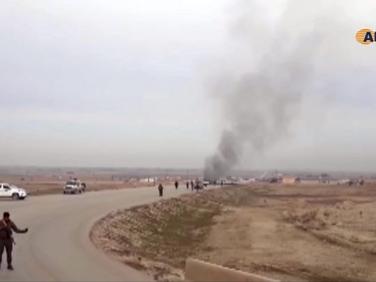 This frame grab from video provided by Hawar News, ANHA, the news agency for the semi-autonomous Kurdish areas in Syria, shows Kurdish fighters standing guard at the site of a suicide attack near the town of Shaddadeh, in Syria's northeastern province of Hassakeh, Syria, Jan. 21, 2019.