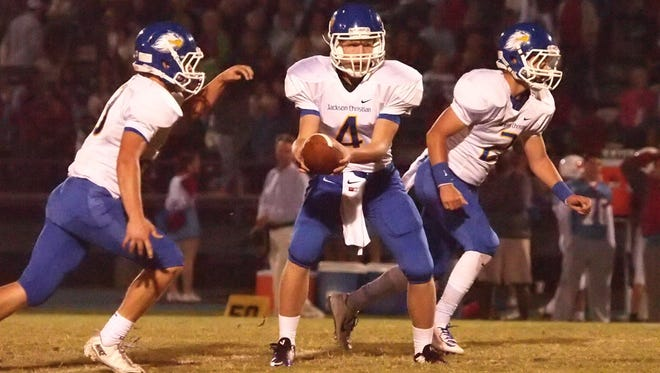 Jackson Christian quarterback Will Buehler hands the ball off to a running back against University School of Jackson during their game last season.