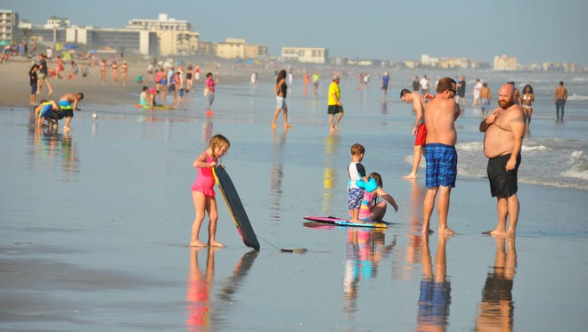 The beach by Minutemen Causeway was crowded Sunday with people taking advantage of the warm weather. The National Weather Service said 2016 was the third-hottest year on record in Melbourne, and 2017 started out warm as well.