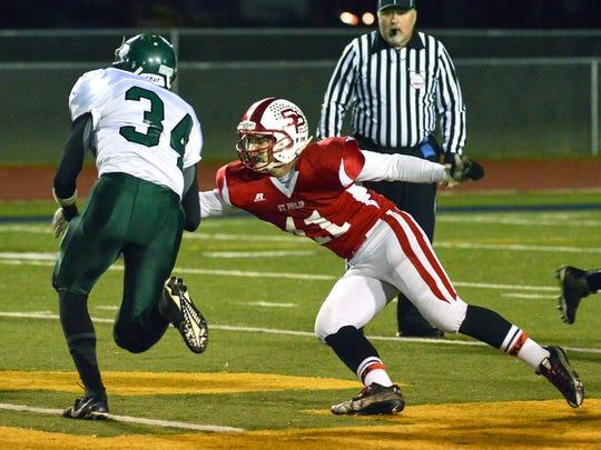St. Philip linebacker Anthony Schaub works to bring down St. Patrick's Brady Lehman.