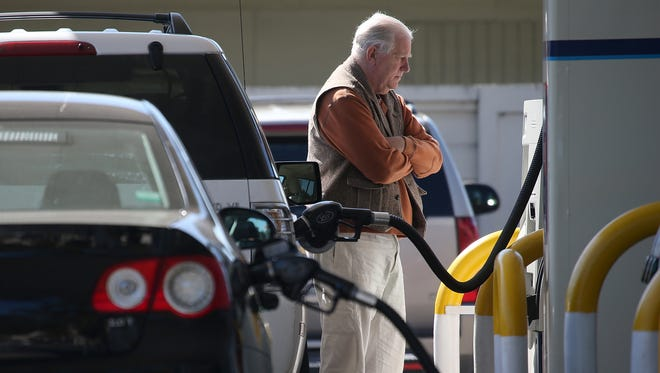 A customer pumps gasoline into his car at an Arco gas station in Mill Valley, Calif.