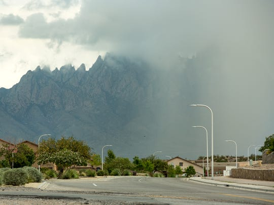A rainstorm, as seen from Calle Jitas, obscures half of the Organ Mountains on Sunday July 23, 201t.