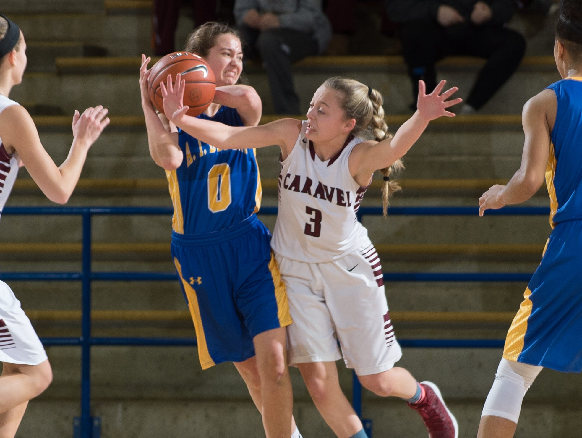Caravel's Karli Cauley (3) knocks the ball from A.I. duPont's Adeline Runco (0) in the quarterfinals of DIAA Girls Basketball Tournament at the University of Delaware.