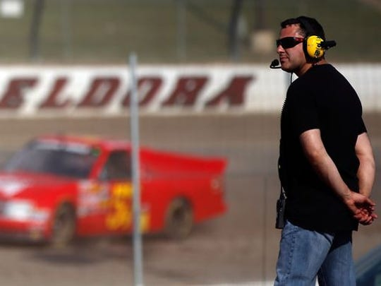 Tony Stewart watches NASCAR trucks practice for the Mudsummer Classic at his Ohio dirt track, Eldora Speedway, in 2013.