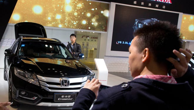 Visitors to the 2014 Energy Saving and New Energy Car Expo this month stand near an SUV displayed in Beijing, China. Analysts expect China to be the biggest market for SUVs in the world by 2018.