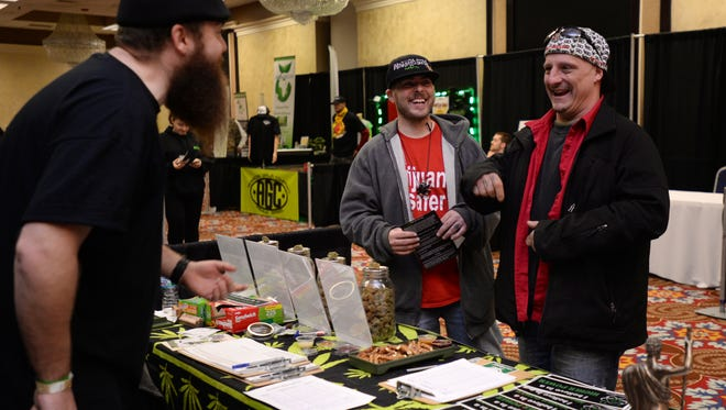 Reverend Jeremy Hall, of the First Cannabis Church of Logic and Reason, left, talks to St. Clair County resident Shaun Vermeulen, center, and Flint resident Joel Stallone during the Extreme Cannquest Expo on Saturday, April 30, 2016 at the Causeway Bay Lansing Hotel & Convention Center in Lansing.
