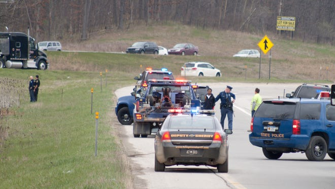 On Friday, police arrested three people, including the one standing near the Michigan State Police trooper in the center of the photo, when they fled from a stolen vehicle and hid in an area of cattails between eastbound I-96 and the M-59 entrance ramp to the freeway.