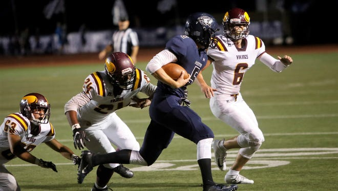 Valley defenders Justice Toomalatai (24) and Garrett Moseley (6) look to bring down Piedra Vista quarterback Trent Kiraly during Friday's game at Hutchison Stadium. PV won, 26-6.