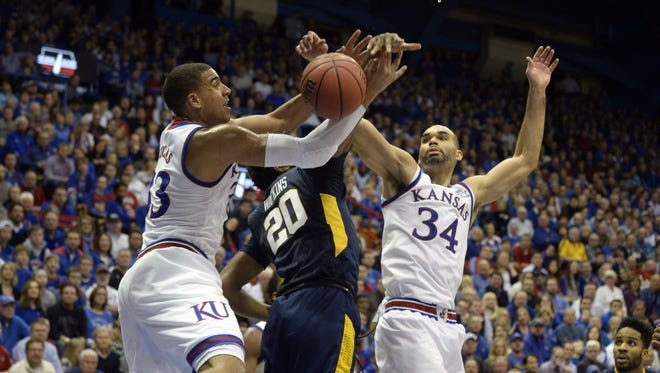 West Virginia Mountaineers forward Brandon Watkins (20) battles for a rebound with Kansas Jayhawks forward Landen Lucas (33) and forward Perry Ellis (34) in the first half at Allen Fieldhouse.