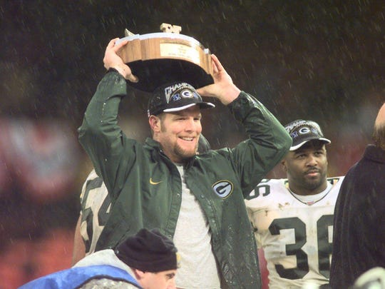 Green Bay Packers quarterback Brett Favre holds the George Halas Trophy over his head as teammate LeRoy Butler stands at his side.