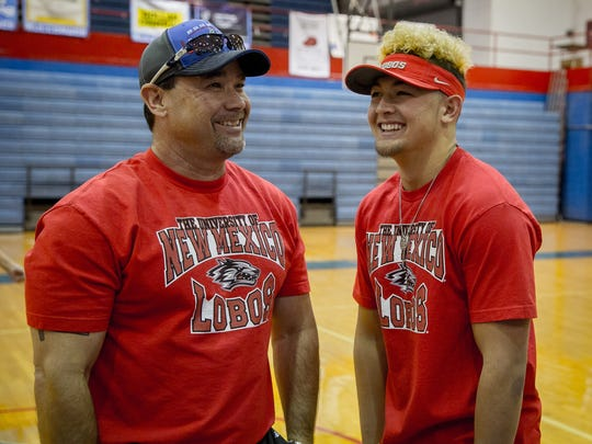 Las Cruces High School football coach Jim Miller, left, jokes with his son, LCHS quarterback Kameron Miller, at the school gymnasium moments before Kameron Miller signs with the University of New Mexico.