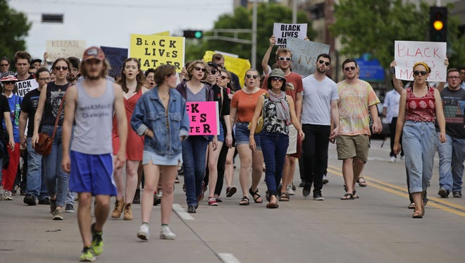 A protest stemming from the fatal police shooting of Jimmie Montel Sanders moves along College Avenue from Houdini Plaza to Jack's Apple Pub on Saturday.