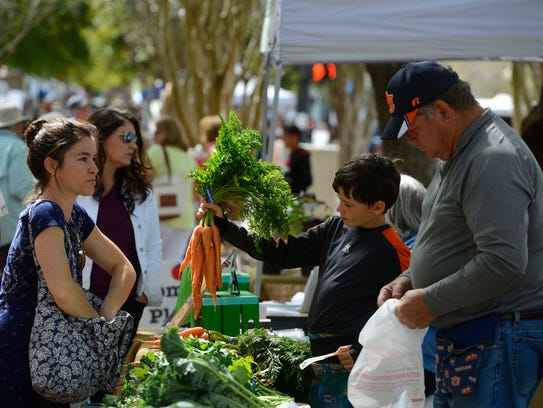 Mathew Cichon of Stewart Farms helps customers Saturday