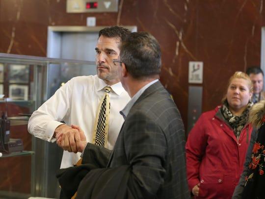 Angelo Ingrassia, left, gets a congratulatory handshake