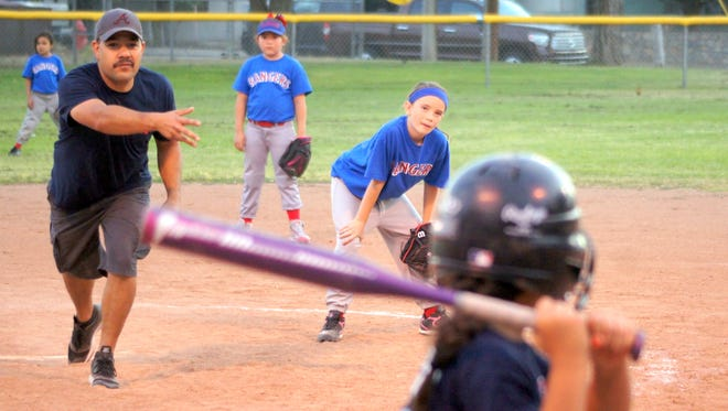 Red ox pitcher Alex Valdespino delivers to the plate while Rangers' pitcher Brooke Wibe looks on to his right. The Deming Coach-Pitch Softball action  plays out nightly at the Lloyd Pratz Recreational Complex on Deming's east side.