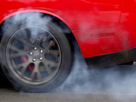 A 2016 Dodge Challenger SRT Hellcat burns rubber while accelerating at full speed down the quarter mile drag strip at the FCA Chelsea Proving Grounds in Chelsea on Thursday, June 23, 2016.