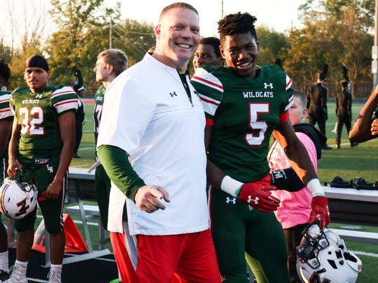 Lawrence North High School football Coach Patrick Mallory walks running back Tre Bonds onto the field during Senior Day.
