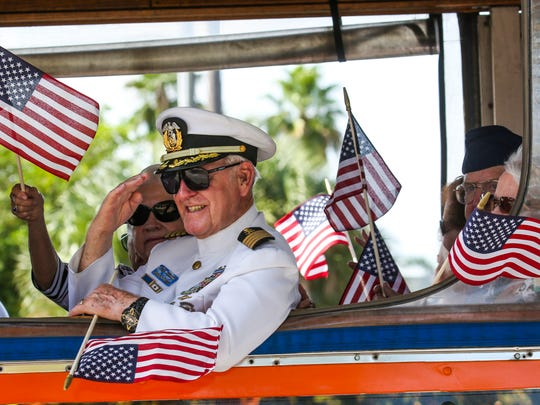 A veteran salutes from the window of the bus he was riding in. A Sept. 11 attacks memorial parade was held in Cape Coral with around 80 participants from EMS, fire, police and military units, marching bands, color guards, special floats, Veterans, etc. The community came out to show their support for the parade participants.