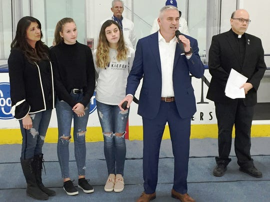 Steven Kiefer (with mike), along with family members Paula, Julianna and Alexa, were joined for the pre-game ceremony by Fr. John Huber, Catholic Central's president.