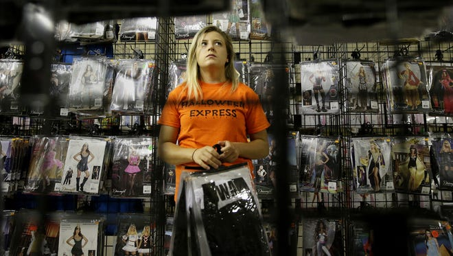 Brianna Baehman organizes costumes last week at Halloween Express in Grand Chute. The store will open Thursday.