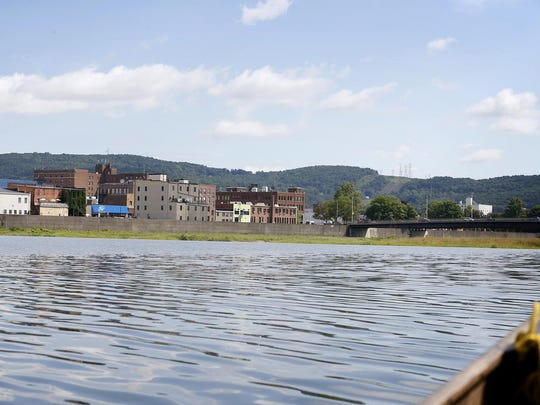 Downtown Elmira buildings on Water Street rise above the Chemung River.