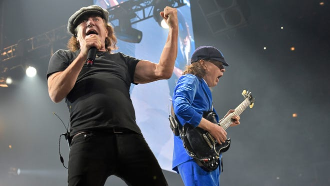 FILE - In this Feb. 17, 2016 file photo, Brian Johnson, left, and Angus Young perform with AC/DC on the Rock or Bust Tour in Chicago.