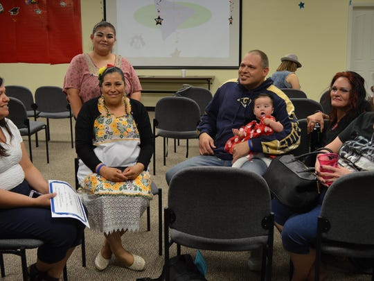 Talking about their experiences after their graduation are translator Leticia Rodriguez, Dayana Breceda (standing), Maria Reyes, Craig Palmer with daughter Annabell, Jamie Bates and her aunt, Cora Gott.